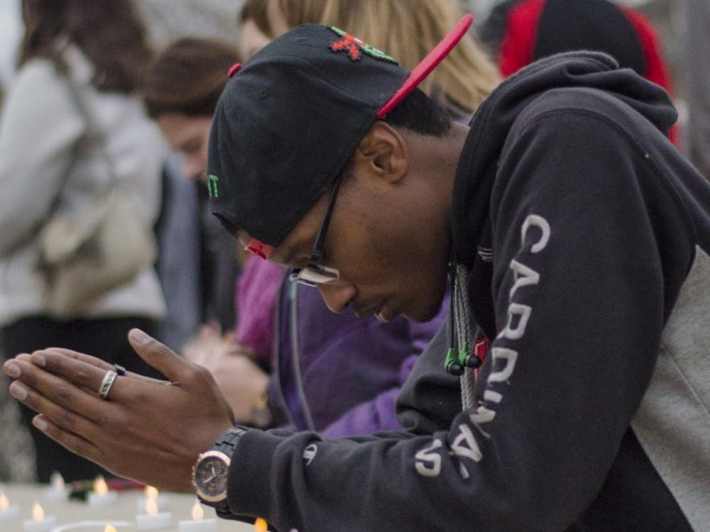 Daishawn Smith, a junior social work major, kneels at Frog Baby to pray on Nov. 16 at the prayer vigil. Those in attendance paid respects to whose lives were lost in Paris, Baghdad and Beirut this weekend. DN PHOTO BREANNA DAUGHERTY
