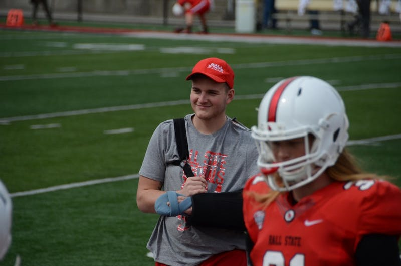 Redshirt freshman Trey Uetrecht stands and smiles on the sidelines with his teammates during the Ball State spring game on April 13 at Scheumann Stadium. The team has rallied around Uetrecht after a car accident that left him critically injured. Zach Piatt, DN