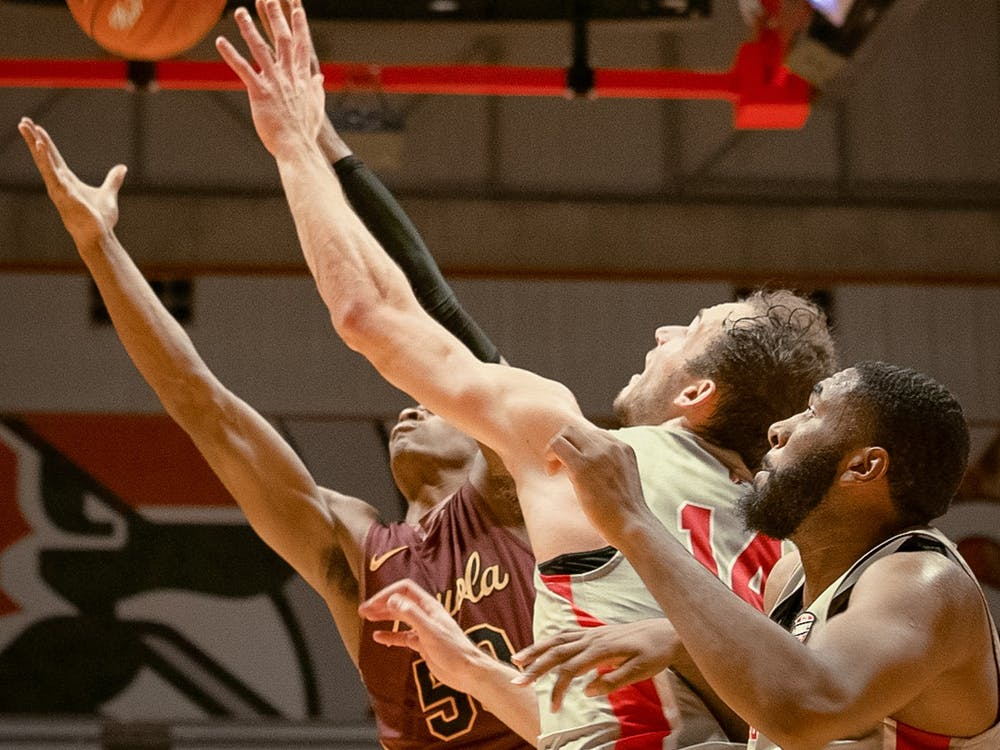 Senior forward, Kyle Mallers (14), attempts to swat the ball away to avoid an opponent rebound against Loyola Chicago Dec. 3, 2019, at John E. Worthen Arena. The Cardinals out rebounded the Ramblers 36-31. Omari Smith, DN