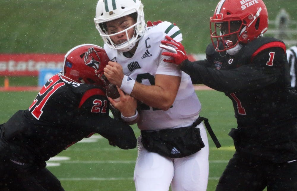 <p>Ball State junior cornerback Antonio Phillips and senior safety Ray Wilborn tackle Ohio quarterback Nathan Rourke during the Cardinals' game against the Bobcats Saturday, Oct. 26, 2019, at Scheumann Stadium. Rourke had 130 rushing yards. <strong>Paige Grider, DN</strong></p>