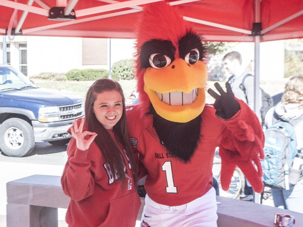 Sophomore medical technology student Shelby Sneed celebrates with Charlie Cardinal at the scramble light after winning the Chirp! Chirp! Spirit Scholarship contest. DN PHOTO COLIN GRYLLS
