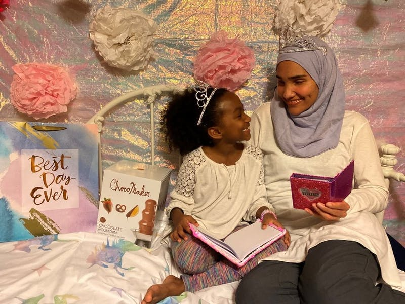 This undated photo shows Melissa Mueller-Douglas and her 7-year-old daughter, Nurah, at their home in Rochester, N.Y. with some of the items they plan to use for a Mother's Day sleepover. Isolation due to the coronavirus outbreak has led mothers and offspring to find creative ways to celebrate. (Yakub Shabazz via AP)
