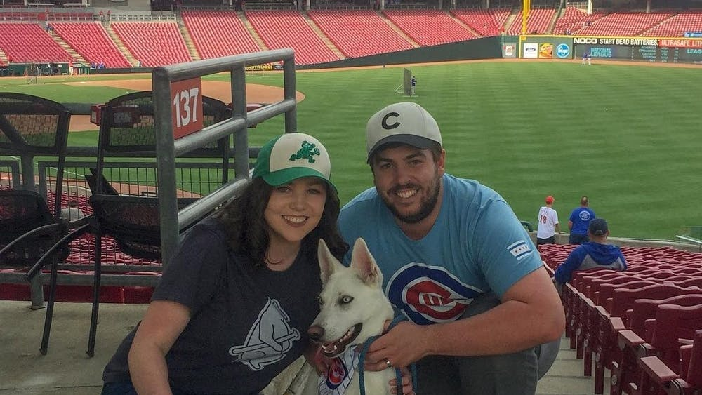 """Sean White, student assistant coordinator, poses with his wife, Heidi, and his husky, Nanuk, May 14, 2019, at the """"Bark in the Park"""" event for the Cincinnati Reds vs. Chicago Cubs game. White said he calls Nanuk """"Nana,"""" and she is enjoying the extra attention she is getting because he is home due to COVID-19 concerns. Sean White, Photo Provided"""