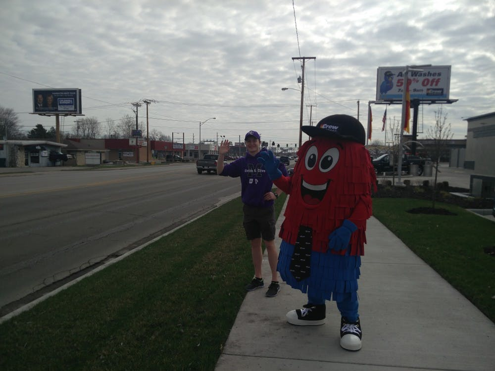 Spinner, the mascot of Crew Carwash, and a volunteer from Muncie Community Schools (MCS) wave at passing vehicles April 6 by the side of McGalliard Road. Crew Carwash is hosting a fundraiser this weekend for MCS at the car wash's McGalliard Road location. Rohith Rao, DN