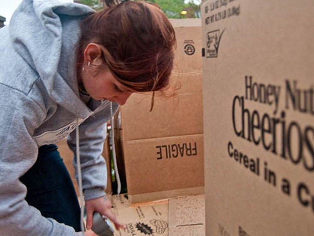 Sophomore Erin Cromer secures the boxes that make up the floor of her house as part of Box City held Friday in front of DeHority. Box City challenges students to spend one night in a cardboard box to bring awareness to the issue of homelessness. DN PHOTO JONATHAN MIKSANEK