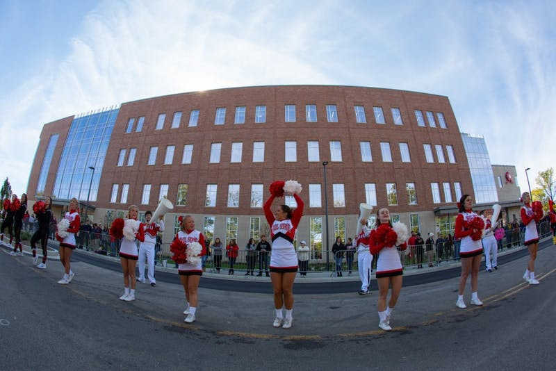 Ball State University cheerleaders kick off the festivities during the Homecoming bed races Oct. 18, 2019 on Riverside Avenue. Bed races have been a Homecoming Week traditional at Ball State since 1980. Kyle Crawford, Byte File