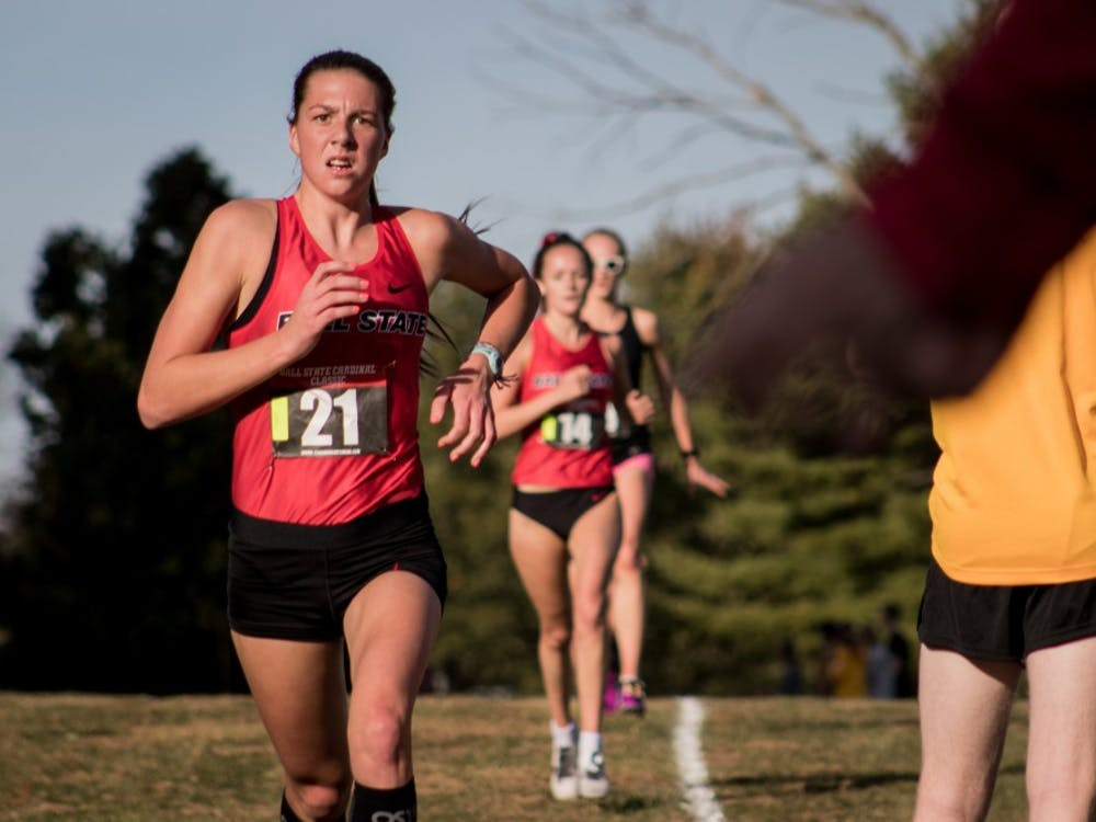 Freshman Juliana Stogsdill runs down the backstretch of the cross country meet as spectators cheer the runners on Oct. 18, 2019, at the Muncie Elks Golf Corse. Ball State Finished first overall for the women with a perfect score. Eric Pritchett, DN