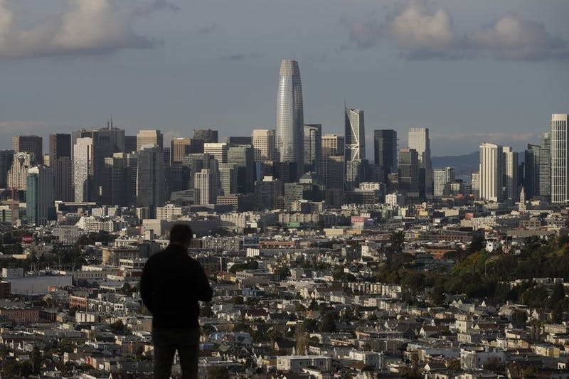 A man looks toward the skyline from Bernal Heights Hill in San Francisco, March 16, 2020. Officials in six San Francisco Bay Area counties issued a shelter-in-place mandate Monday affecting nearly 7 million people, including the city of San Francisco itself. (AP Photo/Jeff Chiu)