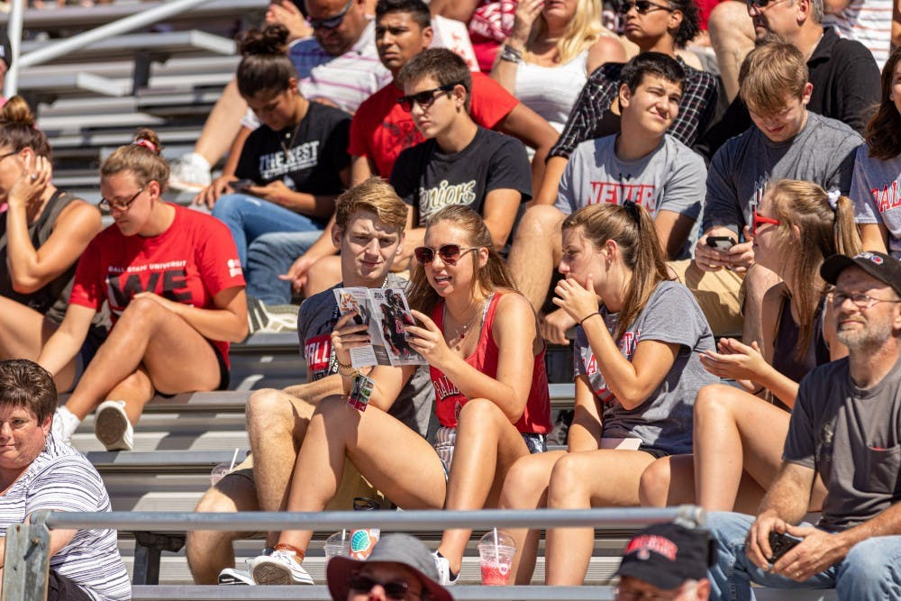 <p>Ball State students use the brochure to follow along with the game on Sept. 14, 2019, at Scheumann Stadium. The family weekend schedule for 2021 includes a football game, children's fair, Emens Auditorium show and a Bell Tower recital. <strong>Paul Kihn, DN File</strong></p>