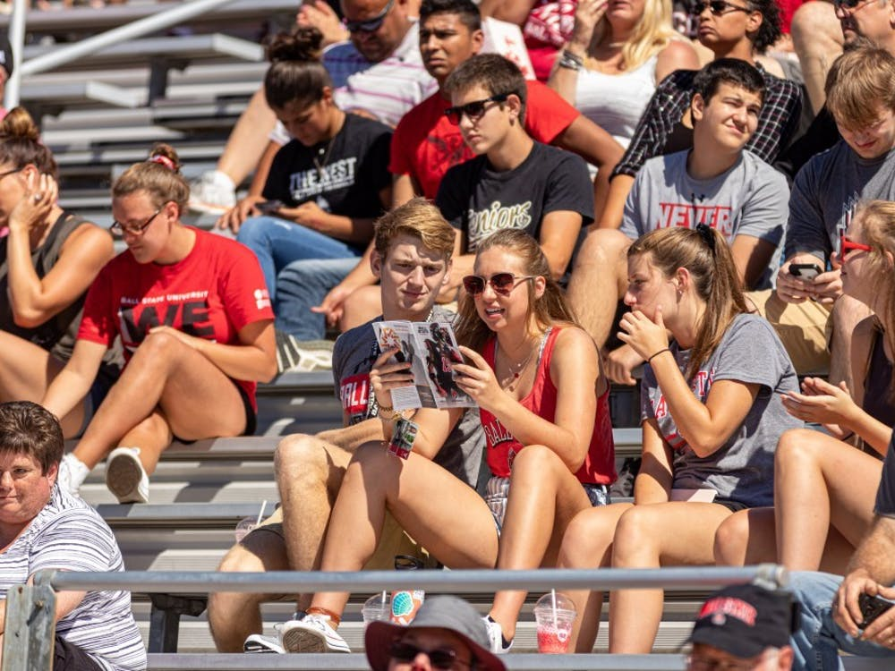 Ball State students use the brochure to follow along with the game on Sept. 14, 2019, at Scheumann Stadium. The family weekend schedule for 2021 includes a football game, children's fair, Emens Auditorium show and a Bell Tower recital. Paul Kihn, DN File
