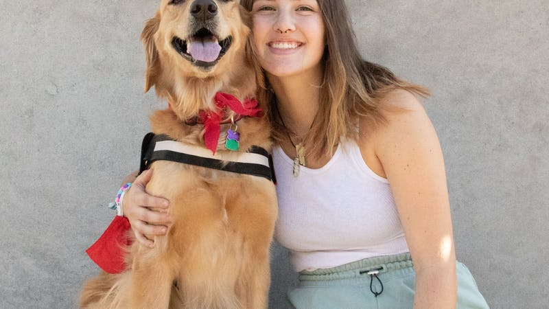 """Sara Harmeyer and her golden retriever, Rey, sit proudly under the bells of Shafer Tower Oct. 1. """"[Rey] goes longboarding with me and we go on lots of walks,"""" Harmeyer said. """"She also gets lots of attention and play time from me and my friends."""" Tori Smith, DN."""