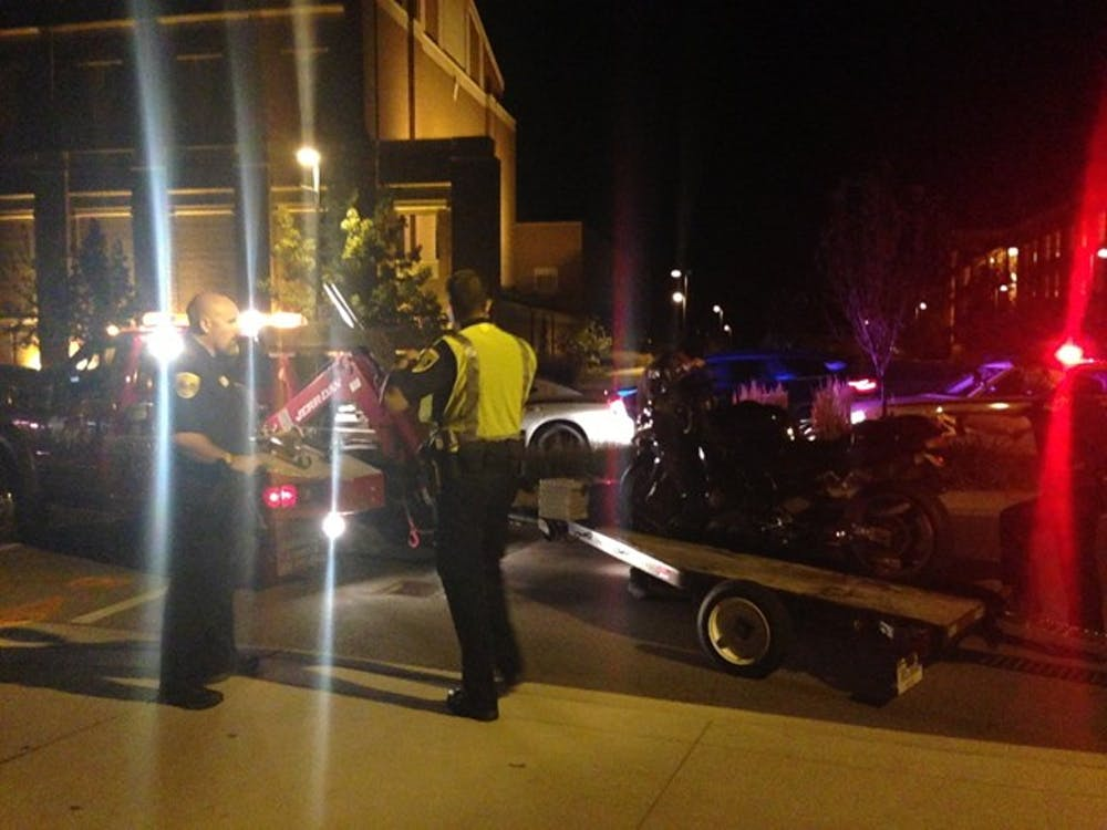 Police remove a motorcycle from the scene of a collision Saturday night near the intersection of McKinley and Riverside Avenues. The driver of the motorcycle was taken to the hospital, and the driver's condition is unknown. DN PHOTO EMMA KATE FITTES