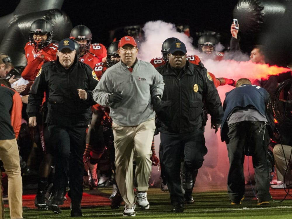 Coach Pete Lembo rushes out onto the field with the Ball State Football team before the game on Wednesday. Ball State lost the game 35-21. DN PHOTO JONATHAN MIKSANEK