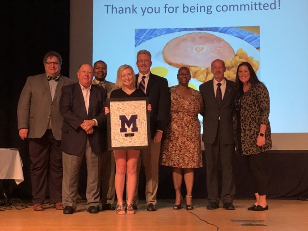 "Allison Polk, Muncie Central High School (MCHS) graduate from the class of 2019, poses for a photo along with other members of Muncie Community Schools board of trustees Aug. 28, 2019, at the board's meeting in the MCHS auditorium. Polk presented the board with the MCHS Varsity ""M"" an award signed by students from the class of 2019. Chris Walker, Photo Courtesy"
