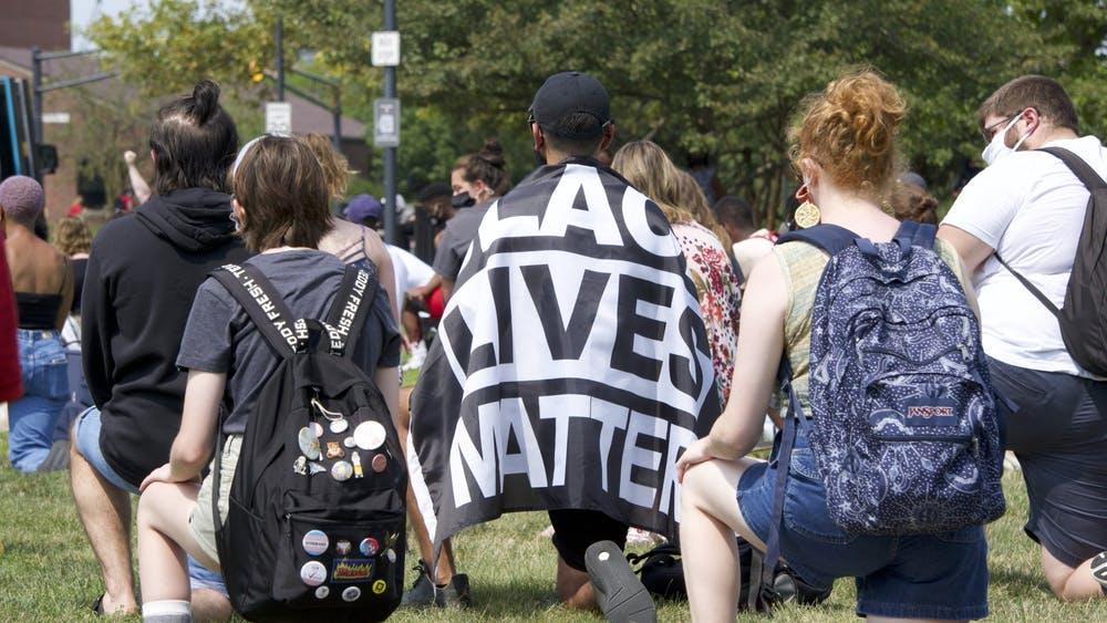 """A protestor wears a """"Black Lives Matter"""" flag while kneeling in memory of George Floyd on the University Green Aug. 25. Taylor Hall, protest organizer and senior public communications major, said she hopes to organize more demonstrations throughout the semester. John Lynch, DN."""