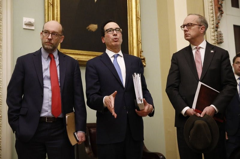 Treasury Secretary Steve Mnuchin, center, speaks with members of the media as he departs a meeting with Senate Republicans on an economic lifeline for Americans affected by the coronavirus outbreak. on Capitol Hill in Washington, Monday, March 16, 2020. (AP Photo/Patrick Semansky)
