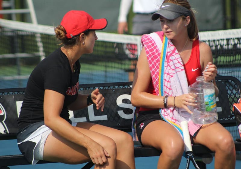 Graduate Assistant Carmen Blanco talks to senior Sarah Swinderski during her first round of singles matches against Detroit Mercy at Cardinal Creek Tennis Center. Swinderski won the first set of the match 6-4. Patrick Murphy,DN