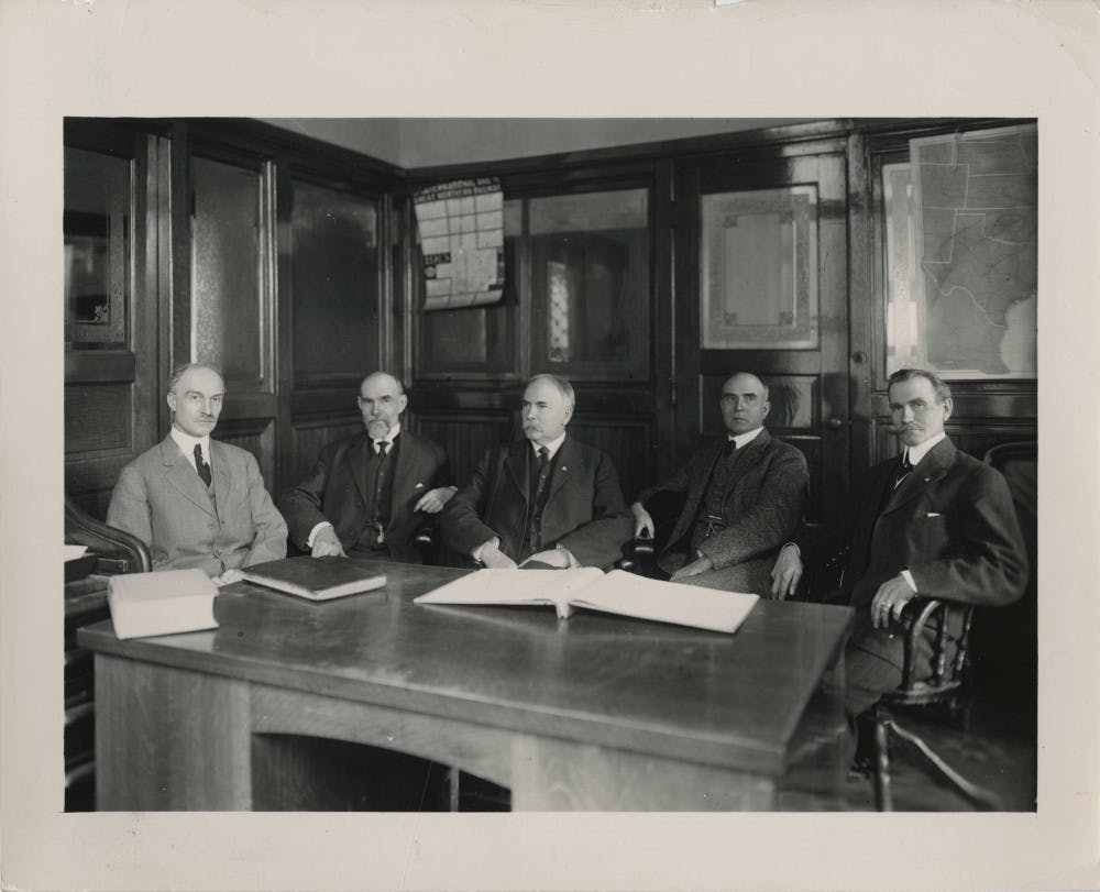 <p>Ball State University founders, George Ball, Lucius Ball, Frank Ball, Edmund Ball and William Ball, sit around a desk. The five Ball brothers bought buildings and grounds of the Muncie National Institute in 1918 and gave the college facilities to the state of Indiana. The college became the Eastern Division of the Indiana State Normal School. <strong>Digital Media Repository Photo</strong>&nbsp;</p>