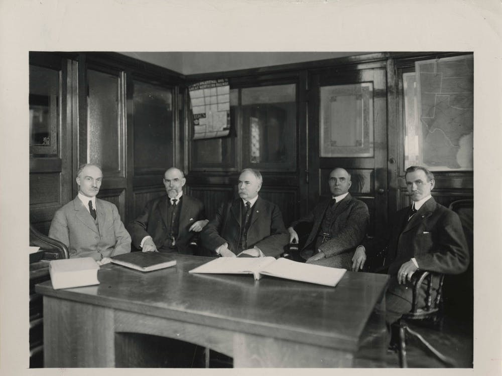 Ball State University founders, George Ball, Lucius Ball, Frank Ball, Edmund Ball and William Ball, sit around a desk. The five Ball brothers bought buildings and grounds of the Muncie National Institute in 1918 and gave the college facilities to the state of Indiana. The college became the Eastern Division of the Indiana State Normal School. Digital Media Repository Photo