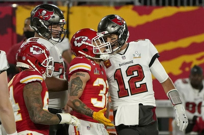 Tampa Bay Buccaneers quarterback Tom Brady (12) talks with Kansas City Chiefs strong safety Tyran Mathieu (32) after throwing a touchdown pass of the NFL Super Bowl 55 football game Sunday, Feb. 7, 2021, in Tampa, Fla. (AP Photo/Gregory Bull)