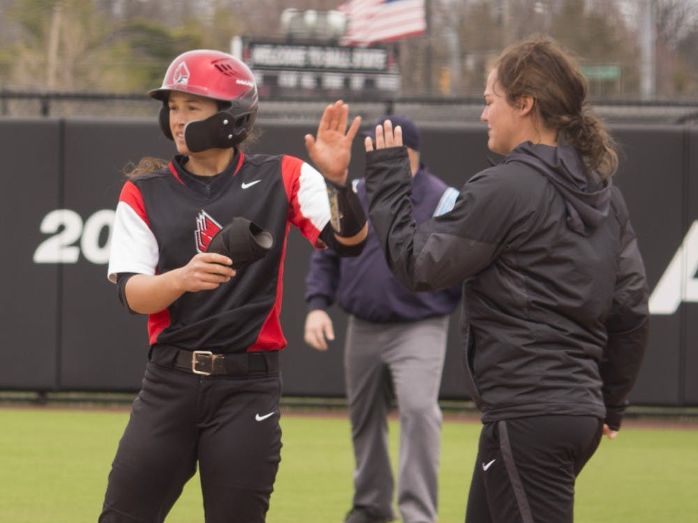 Ball State senior Maddy Labrador, left, high fives volunteer assistant coach Rachel Houck during the first game against Central Michigan April 21 at the softball field at First Merchant's Ballpark Complex. Ball State won the first game 2-1. Briana Hale, DN