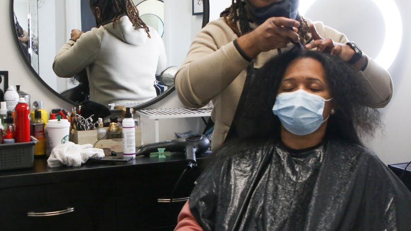 Che Hopkins, owner of Meraki Style Studio, parts Rachelle Joyner's hair to blow dry for a silk press March 12, 2021. Joyner said she drove from Indianapolis, Indiana, to get her hair down by Hopkins as he has been her stylist for 13 years. Sumayyah Muhammad, DN.