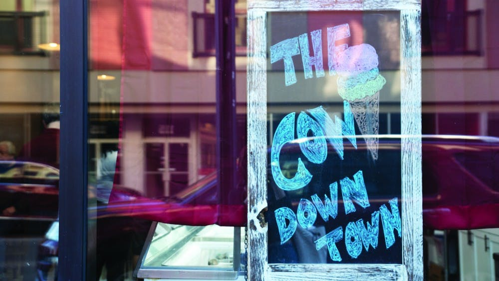 """A sign in the window of The Barking Cow displays the ice cream shop's nickname, """"The Cow Downtown."""" Manager Danielle Woodson gave this nickname to The Barking Cow because in Gaston, locals call the ice cream shop, """"The Cow."""" Pauleina Brunnemer, DN"""