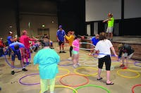 Camp ReYoAd campers play a game with hoola hoops in the recreational room during summer 2018. Camp ReYoAd provides summer experiences for individuals with special needs aged 16 and older. Molly Boylan, photo provided.