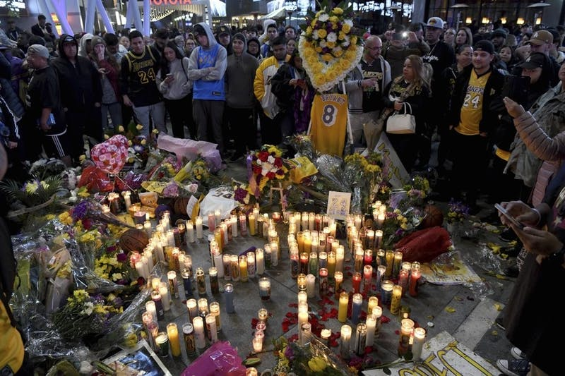People gather at a memorial near Staples Center Jan. 26, 2020, in Los Angeles after the death of Laker legend Kobe Bryant. (AP Photo/Michael Owen Baker)