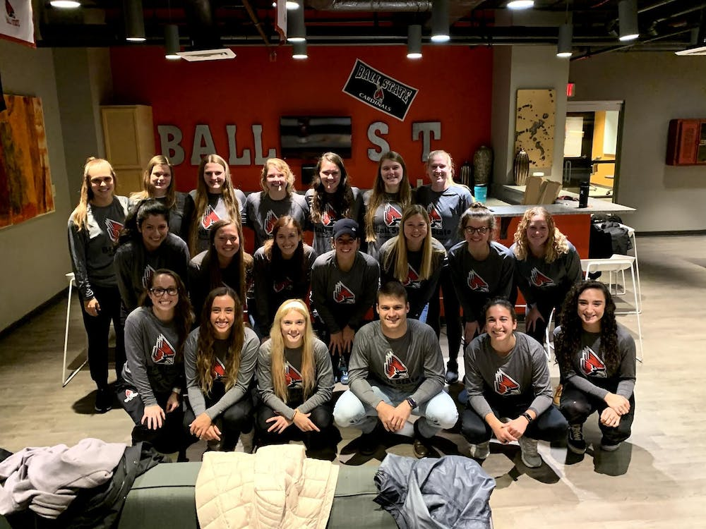 <p>Ball State women's club soccer head coach Alex Davidson poses with his players during a team banquet. Alex and his brother Andy have followed their mother's footsteps in coaching the team. Alex Davidson, photo provided</p>