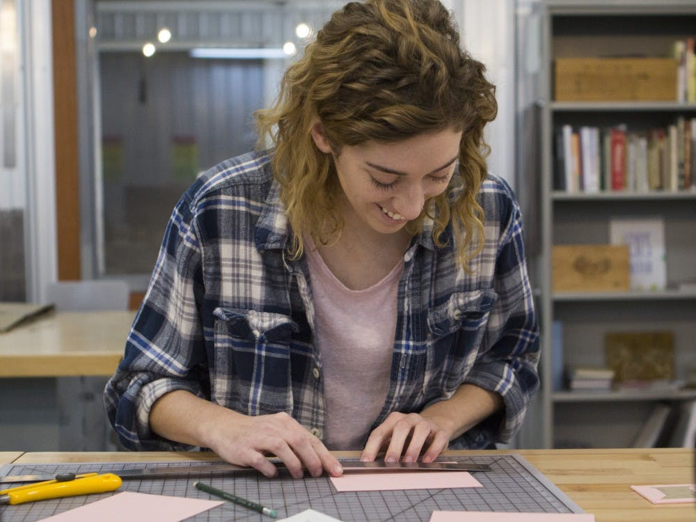 Gipson Schabel, a senior actuarial science major, works on making miniature books at the Book Arts Collaborative in downtown Muncie. Emma Rogers // DN