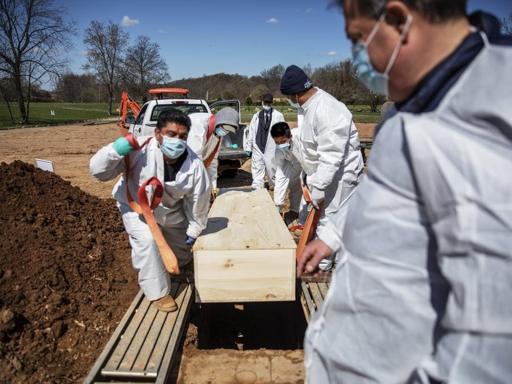 In this April 6, 2020 photo, gravediggers lower the casket of someone who died of coronavirus at the Hebrew Free Burial Association's cemetery in the Staten Island borough of New York. (AP Photo/David Goldman, File)