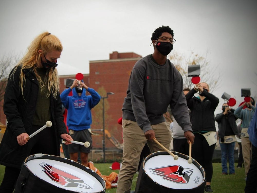 Junior music education major AnnaMarie Kelly (left) plays the bass drum during a Ball State Pride of Mid-America (POMA) Marching Band rehearsal this semester on LaFollette Field. The POMA Marching Band was split into three bands to ensure social distancing during rehearsals. Bethany Sloniker, Photo Courtesy