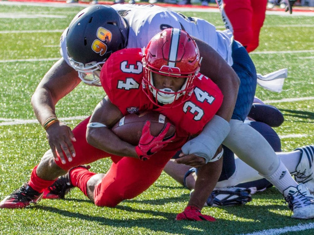 Ball State's running back James Gilbert is tackled by an Akron player during the game on Oct. 22 in Scheumann Stadium. The Cardinals lost 25 to 35. Grace Ramey, DN