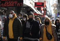 People wearing masks to help protect against the spread of coronavirus, walk in Ankara, Turkey, Friday, Nov. 27, 2020. The official daily COVID-19 deaths have steadily risen to record numbers in a reversal of fortune for the country that had been praised for managing to keep fatalities low. (AP Photo/Burhan Ozbilici)
