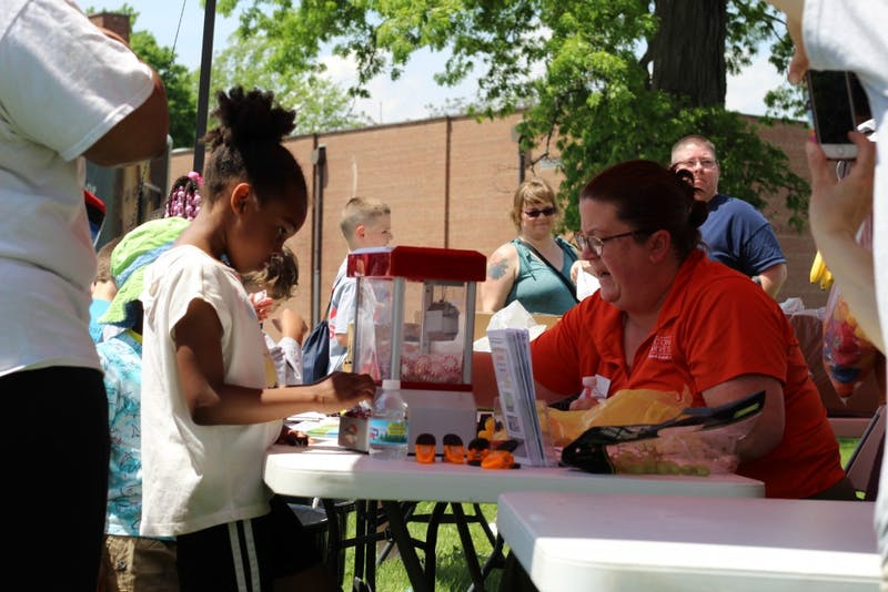 Stacey Ream-Britton, research development coach for Second Harvest Food Bank, works a her station as a participant stands by at Ball State's Community Campus Experience event May 18, 2019, at Heekin Park. Second Harvest distributed fruits to those in attendance. Britney S. Kendrick, DN
