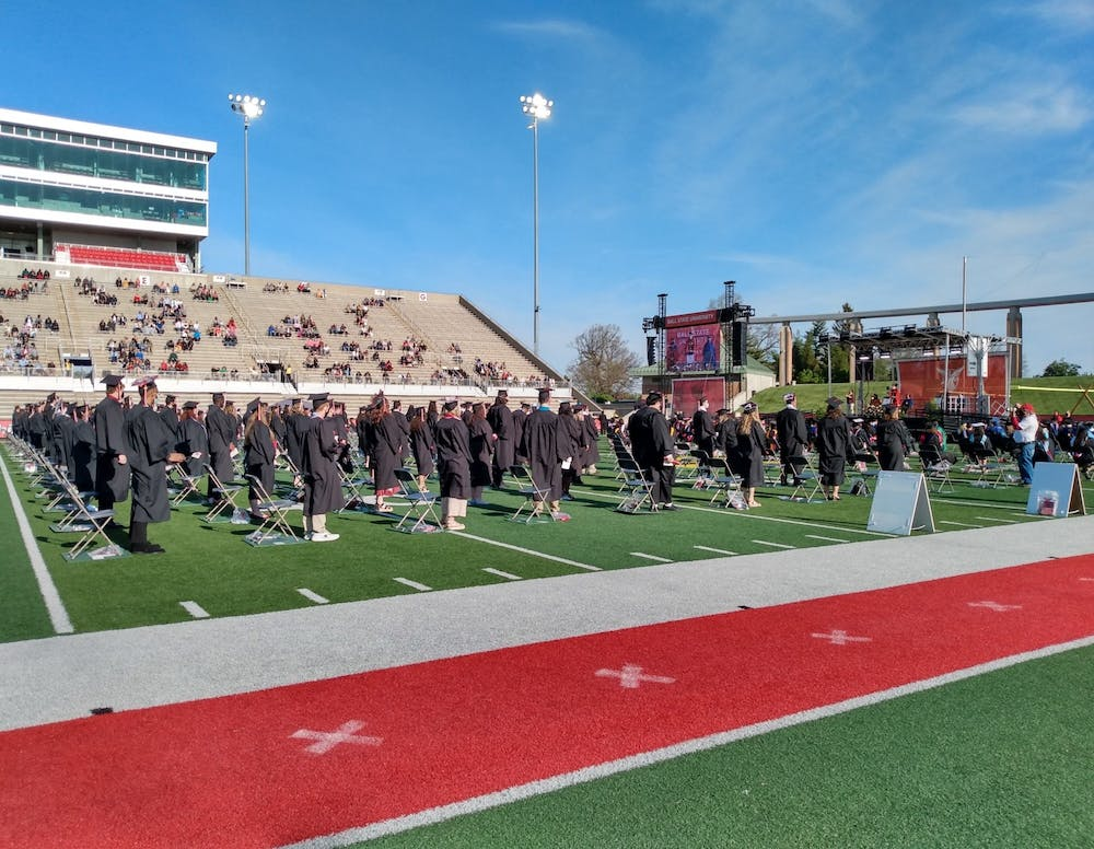 <p>Ball State graduates from the classes of 2020 gather on the Scheumann Stadium turf May 15, 2021. Due to COVID-19, the university delayed commencement for a year, but invited graduates back to campus for a ceremony in spring 2021. <strong>Maya Wilkins, DN File</strong></p>