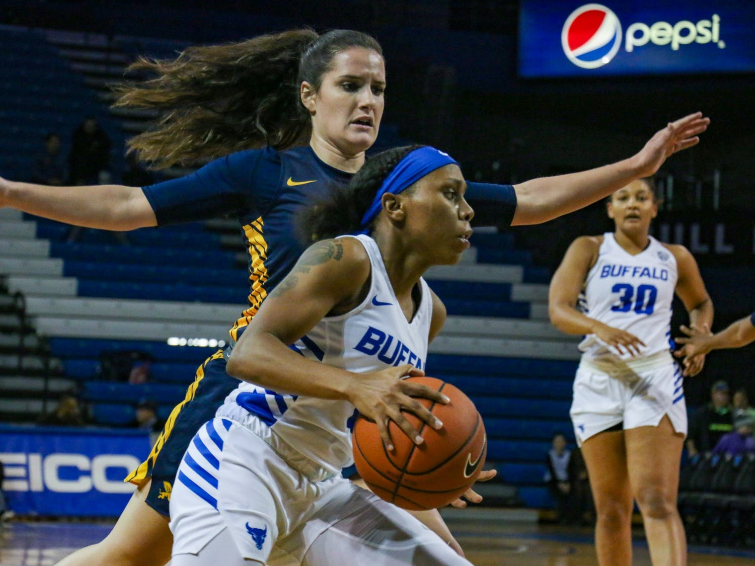 Dyaisha Fair protects the ball from a Canisius defender Tuesday night during UB's victory.