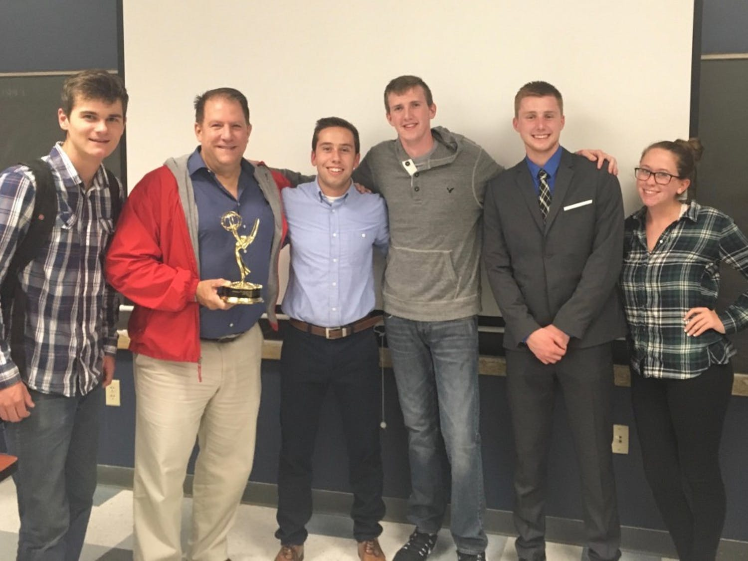 Accounting major Benjamin Corbett (third from left) stands with club members and guest speaker Dave Cash, an Emmy-winning Channel 2 News Reporter (second from left) at a weekly DECA meeting.  Corbett founded UB DECA, a club focused on building business and entrepreneurial skills, after transferring to UB.