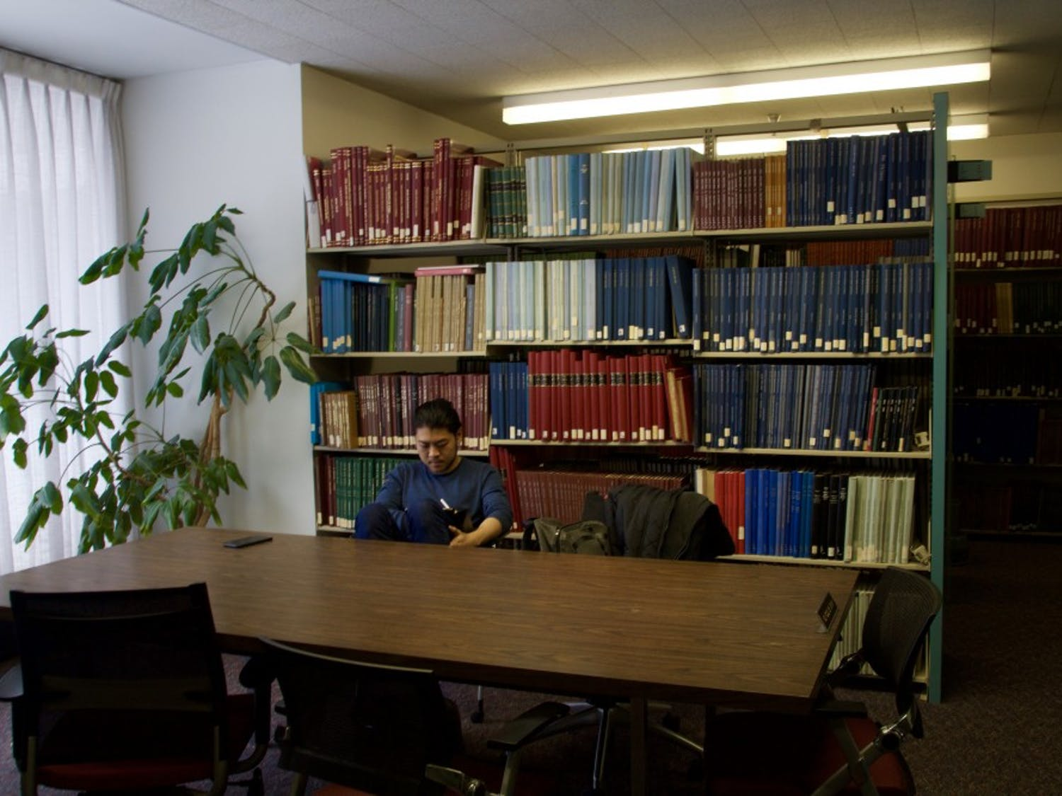 A student reads a book inside the Music Library alone. Faculty and students still have concerns over the library's future, following the retirement of the library's archivist.