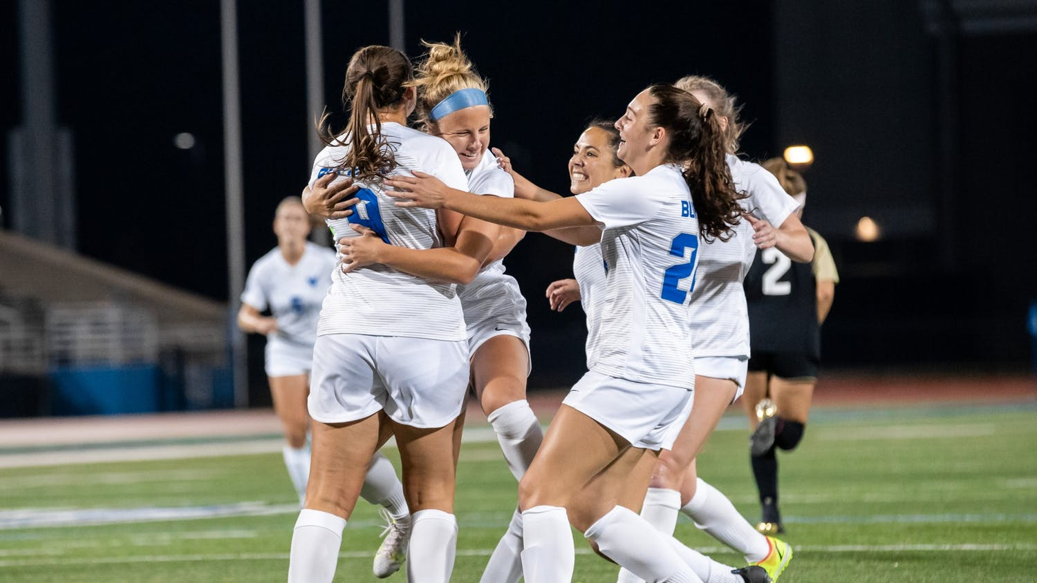 Gianna Yurchak (9), Kaya Schultz (24) and members of the women's soccer team celebrate after scoring a goal over the weekend.