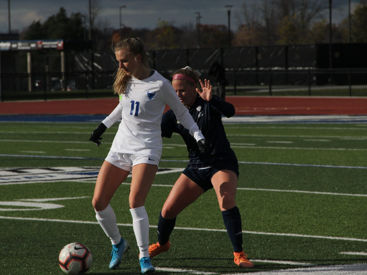 UB midfielder Marcy Barberic (11) defends the ball from Akron during the 2019 MAC Quarterfinals.