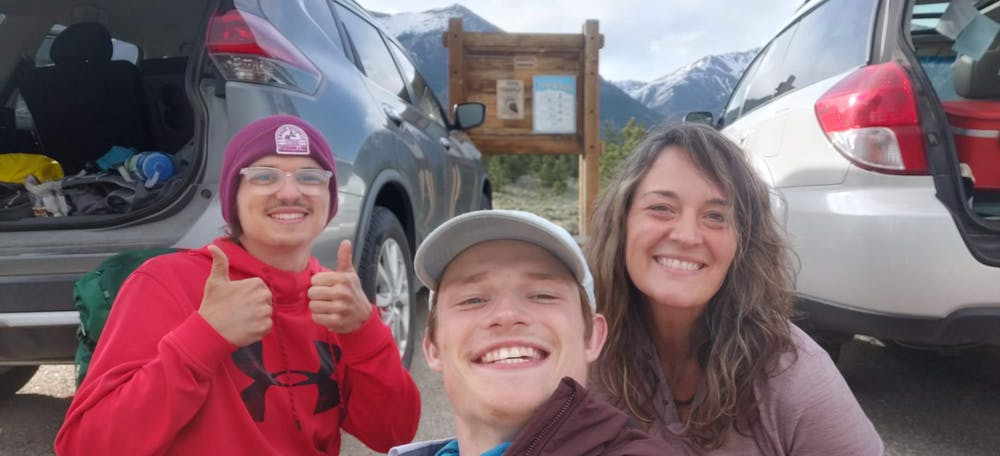 <p>Collin Searles (left) and Nick Metz (center) pose with an unknown woman at a trail head.</p>