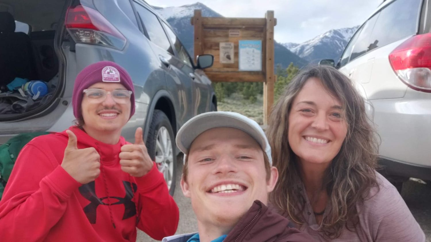 Collin Searles (left) and Nick Metz (center) pose with an unknown woman at a trail head.
