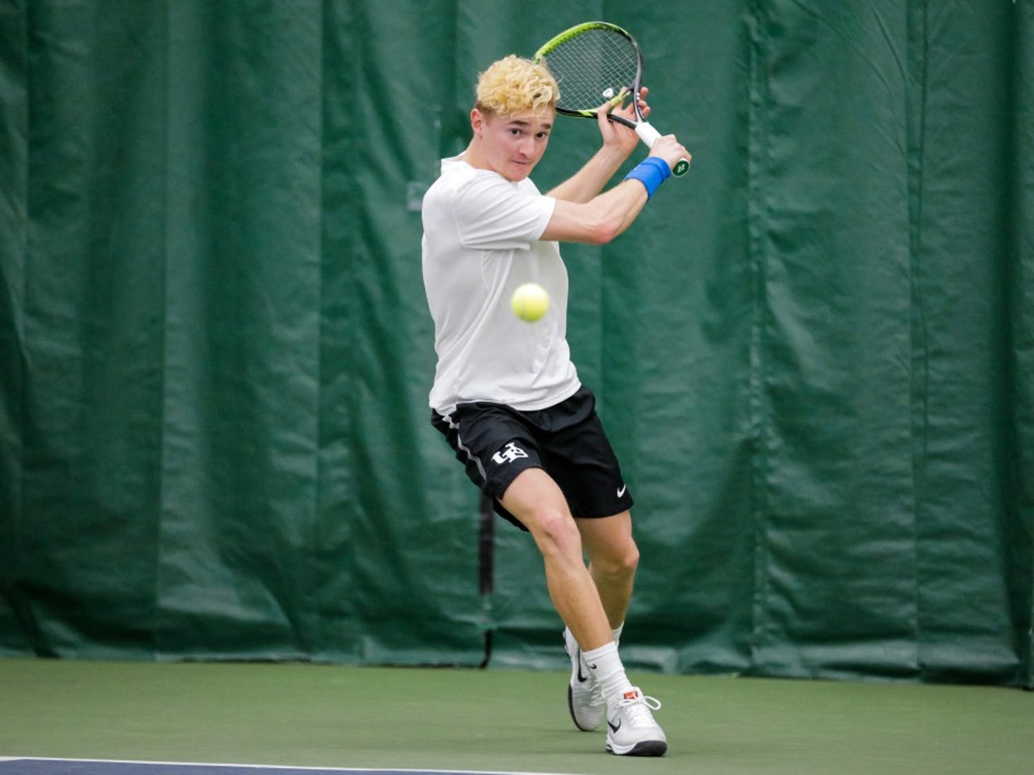 Freshman Nickolas Frisk prepares to hit the ball with a back hand. The Bulls picked up two wins this weekend to improve its conference record to 3-1.