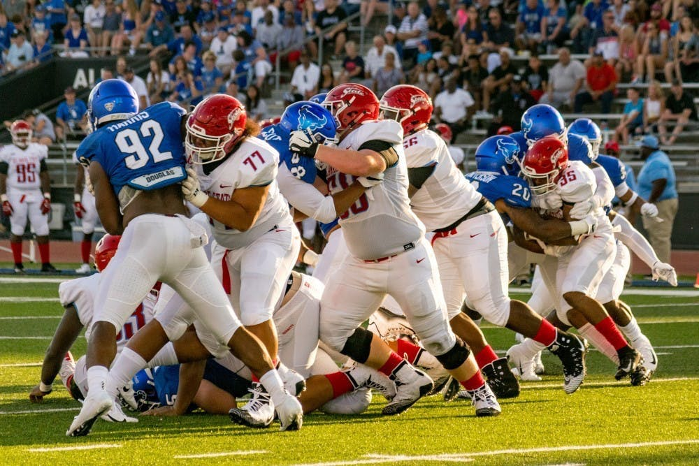 <p>Senior defensive end Chuck Harris tries to push through the Delaware State offensive line. The Bulls handily beat Delaware State 48-10 last season.</p>