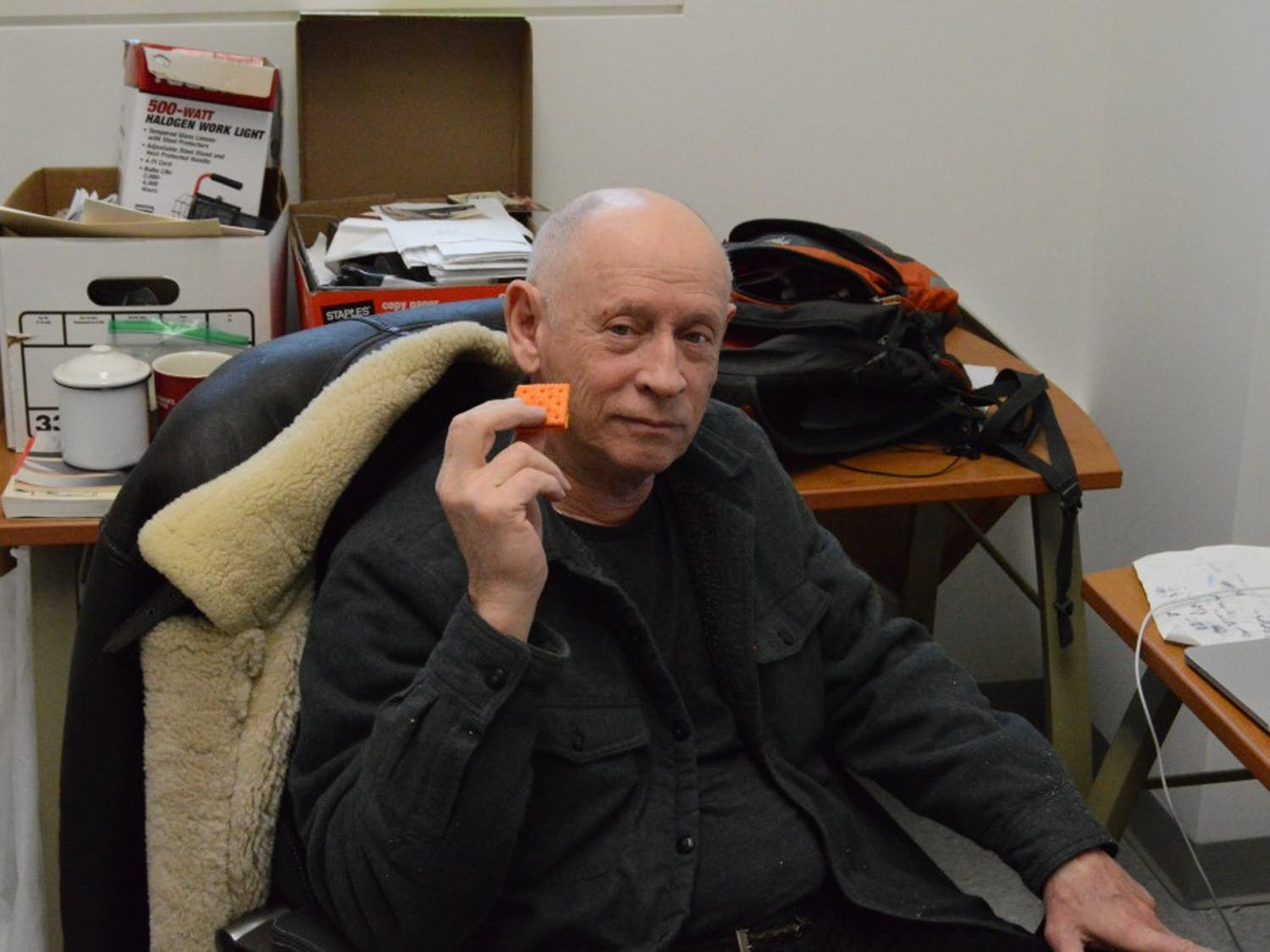 UB professor David Schirm enjoys a cheese and peanut butter cracker in his office. Schirm, a celebrated artist and tenured professor, is set to retire in 2020.
