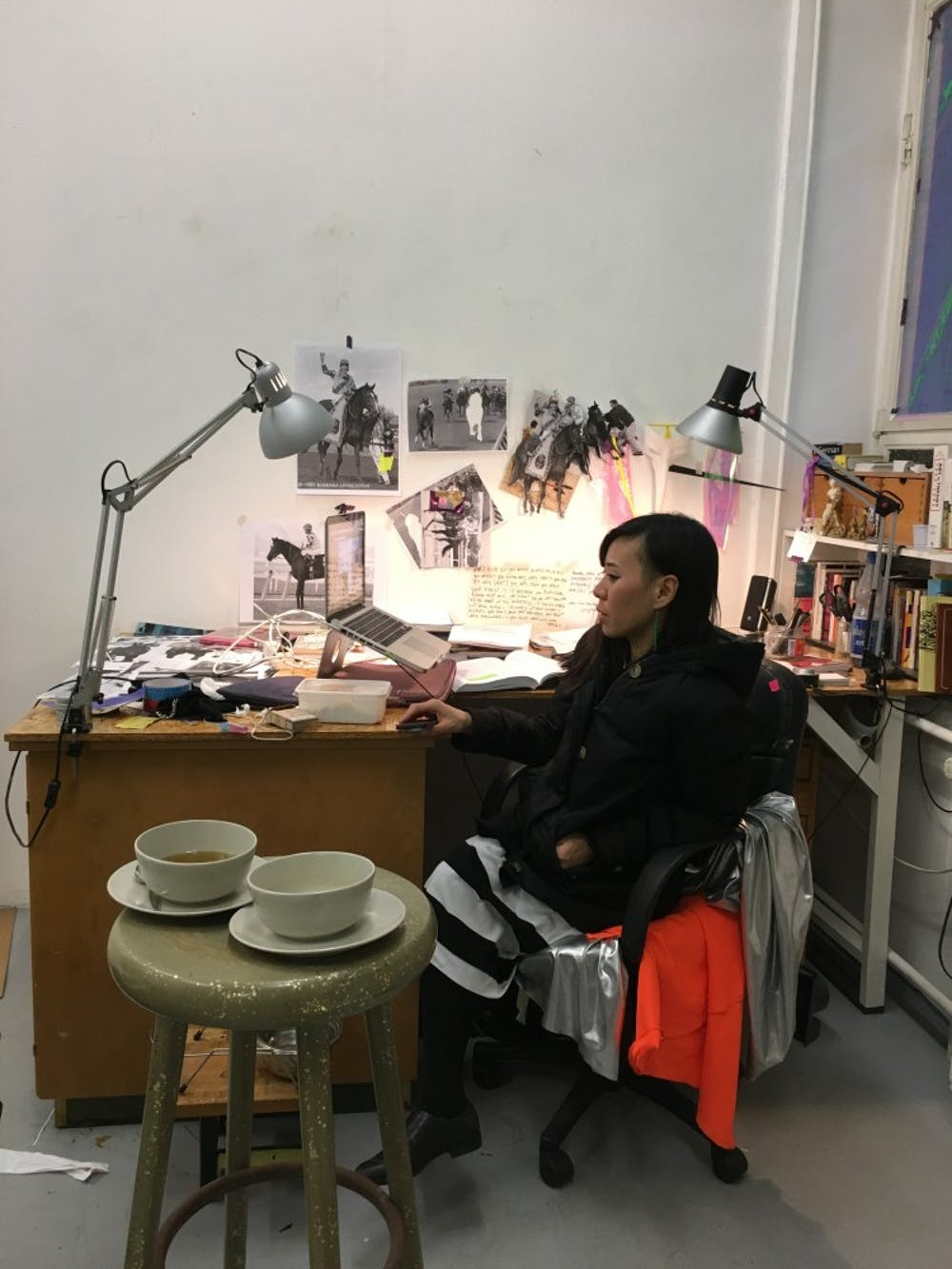 <p>Christa Joo Hyun D'Angelo works at her desk in her Kreuzberg studio. She is currently completing an exhibition focusing on the inhumanity of horse racing, another example of politically-charged work given a platform in Berlin's art scene.</p>