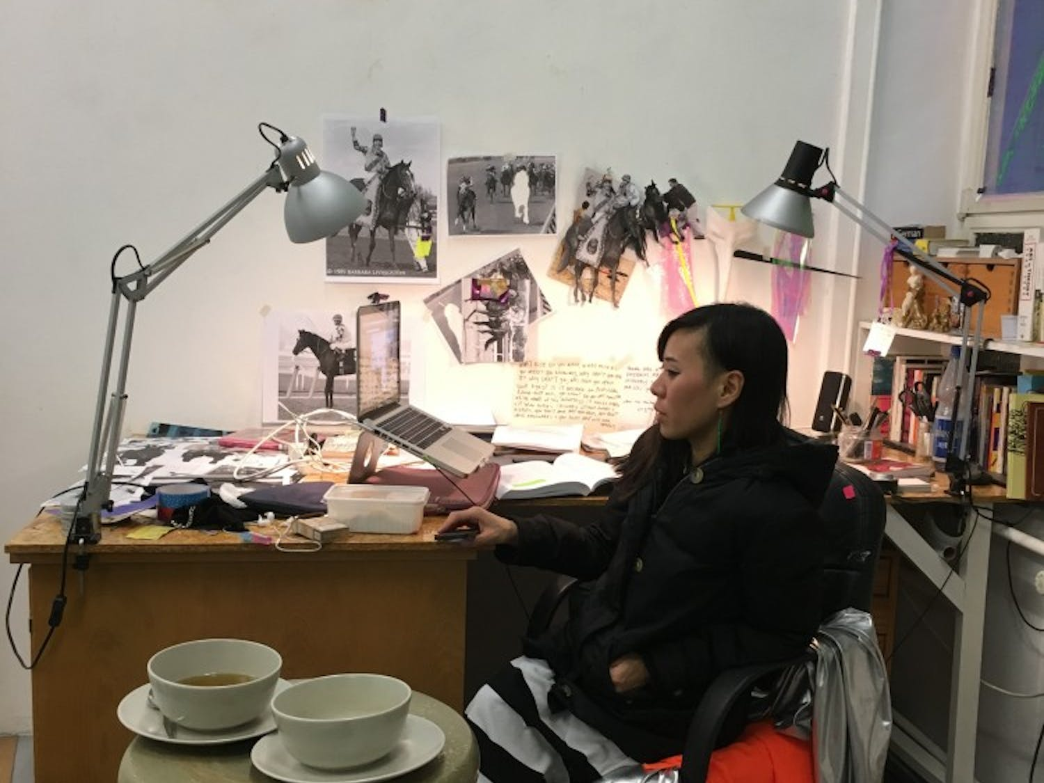 Christa Joo Hyun D'Angelo works at her desk in her Kreuzberg studio. She is currently completing an exhibition focusing on the inhumanity of horse racing, another example of politically-charged work given a platform in Berlin's art scene.