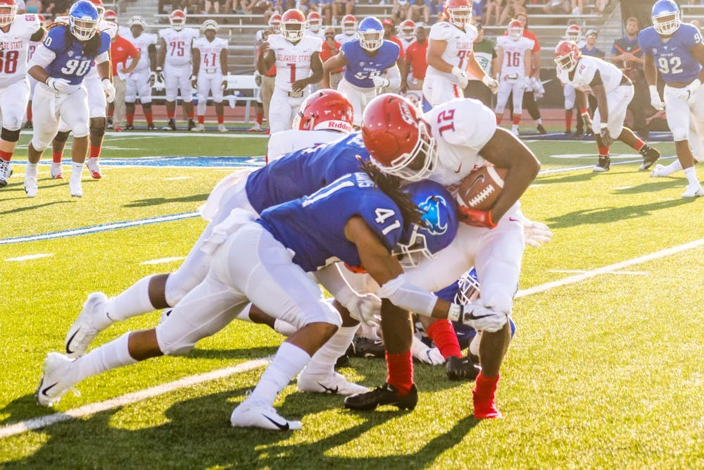 <p>Senior free safety Brandon Williams tackles a Delaware State player. Williams typically wears number 14 but wore number 41 in Saturday's game to honor teammate Solomon Jackson.</p>
